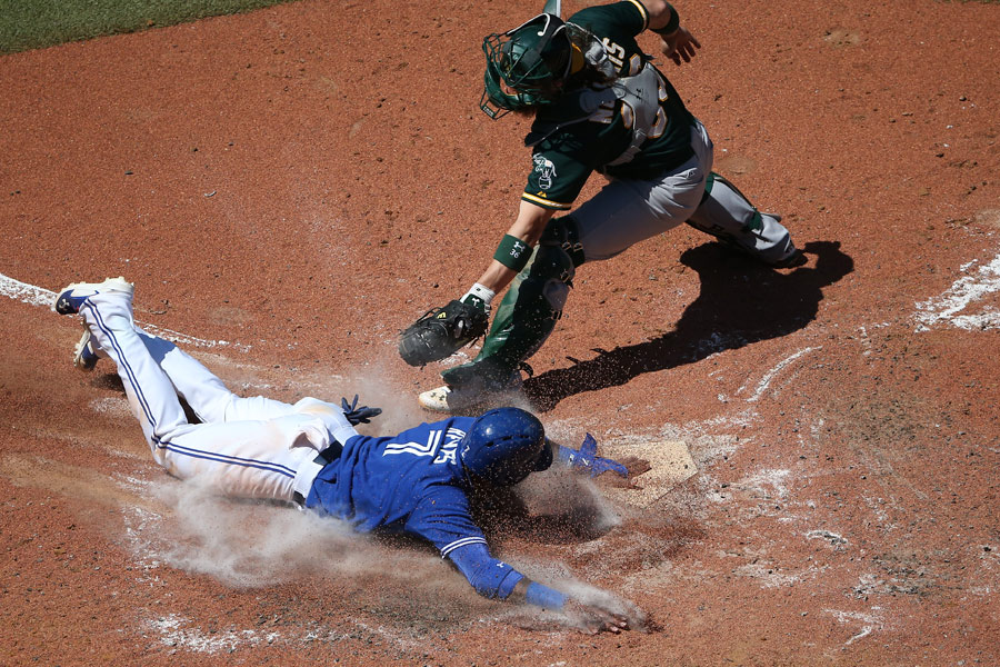 Jose Reyes of the Toronto Blue Jays slides safely into home plate to score a run as Derek Norris of the Oakland Athletics swipes in an attempt to tag him