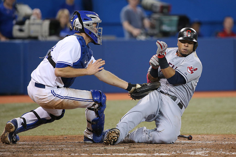 Carlos Santana of the Cleveland Indians is tagged out at home plate in the eighth inning by Josh Thole of the Toronto Blue Jays