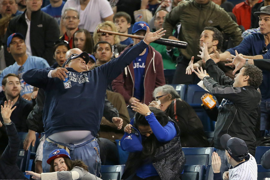 A New York Yankees' fan reaches for a stray bat while holding on to his drink as the bat goes into the stands after Brian Roberts(not pictured) lost his handle while swinging against the Toronto Blue Jays
