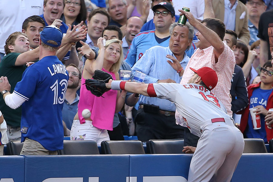 Matt Carpenter of the St. Louis Cardinals goes after a foul pop up, but comes up short in a game against the Toronto Blue Jays