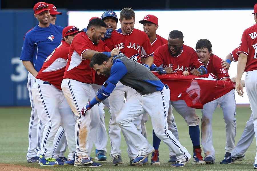 Jose Bautista is feted by teammates after ending the longest game in Toronto Blue Jays history with an RBI single in the 19th inning