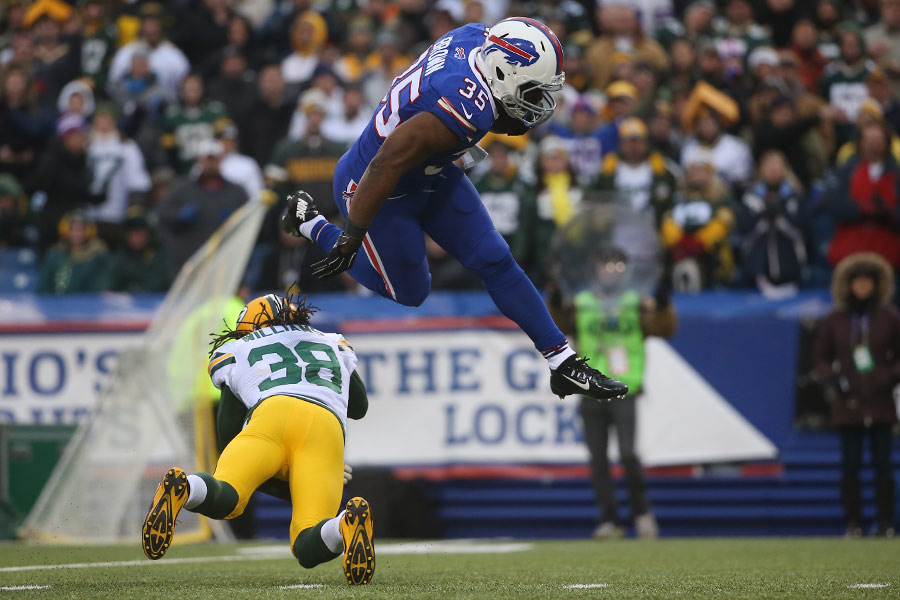 Bryce Brown of the Buffalo Bills hurdles over Tramon Williams of the Green Bay Packers as he carries the ball