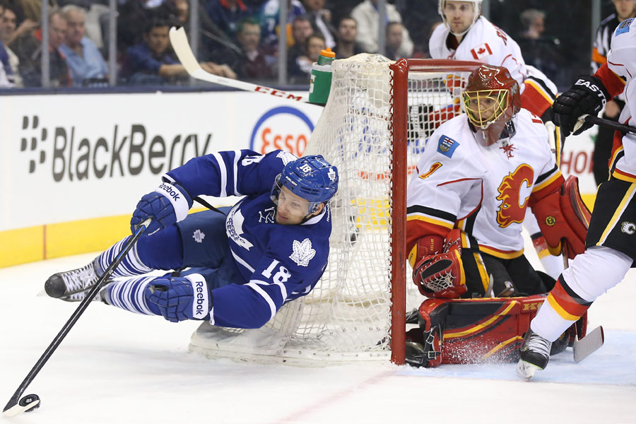 Toronto Maple Leafs right wing Richard Panik falls as he tries to skate around the net as Calgary Flames goalie Jonas Hiller guards said net