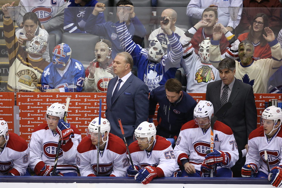 Fans dressed as vintage goalies watch the game from behind the Montreal Canadiens bench as head coach Michel Therrien looks on