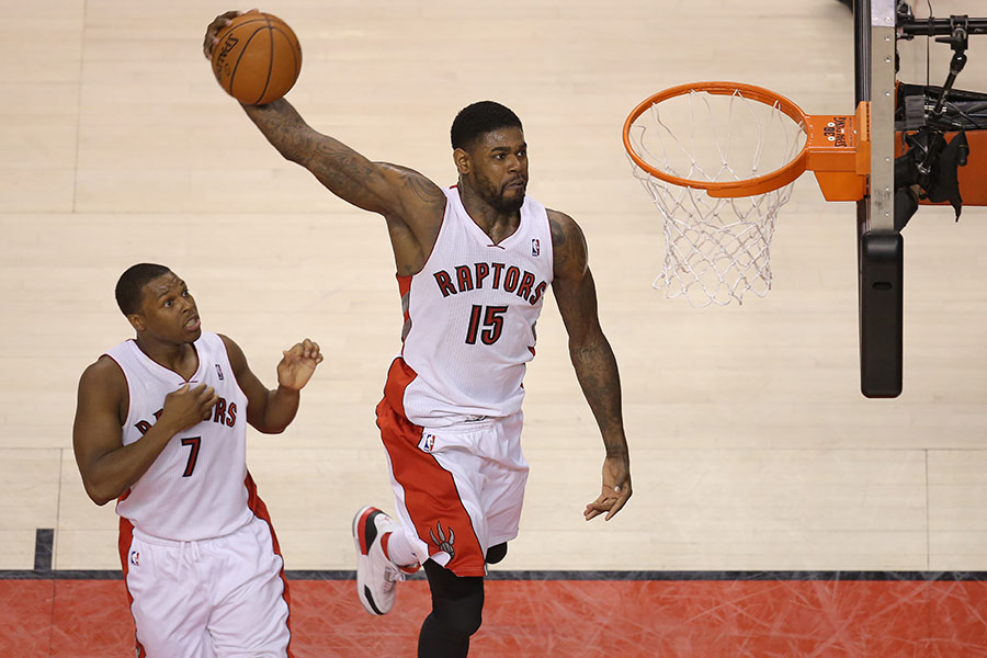 Amir Johnson of the Toronto Raptors power dunks as Kyle Lowry watches