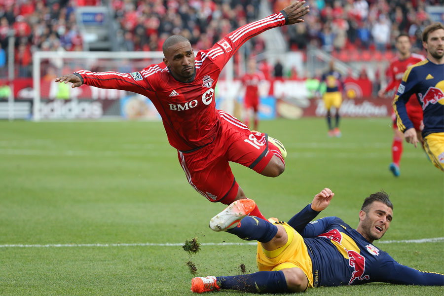 Toronto FC forward Jermain Defoe is sent airborne by the defender after scoring a goal