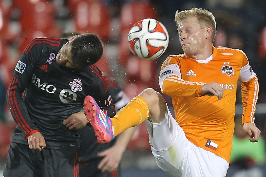 Houston Dynamo midfielder Andrew Driver tries to play the ball with his foot as Toronto FC defender Mark Bloom goes at it with the head