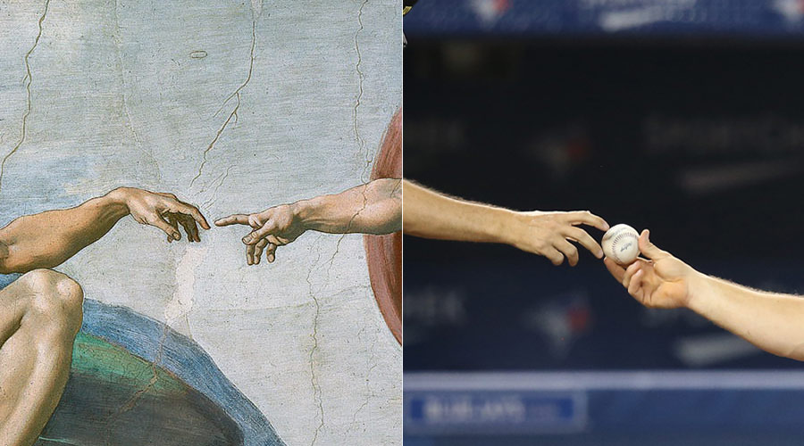 Michelangelo?s ?Creation of Adam? painting is mimicked by Paul Emmel(L) and Erik Kratz(R) here as a baseball is exchanged