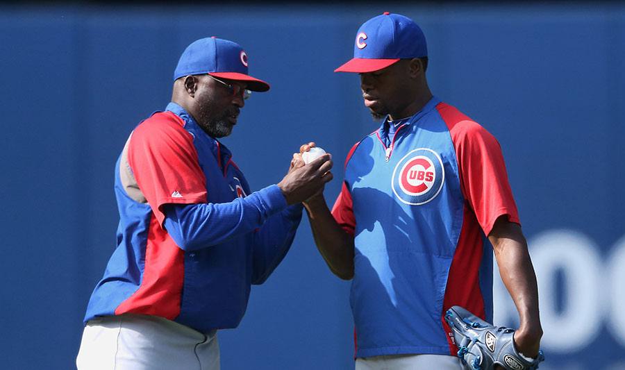 Bullpen coach Lester Strode works on a grip with pitcher Arodys Vizcaino