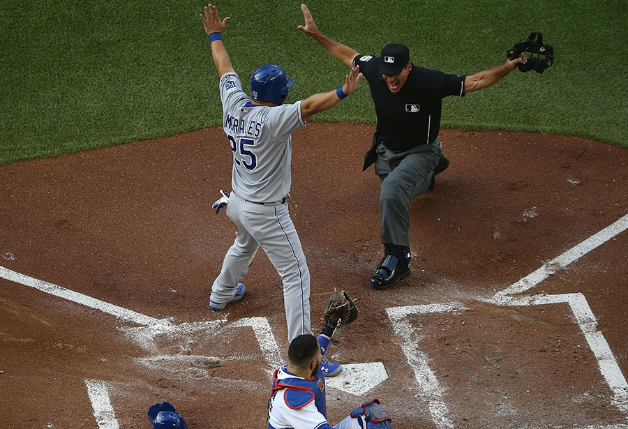 Simon says stretch your arms out :  Kendrys Morales helps home plate umpire Angel Hernandez make the safe call to score a run