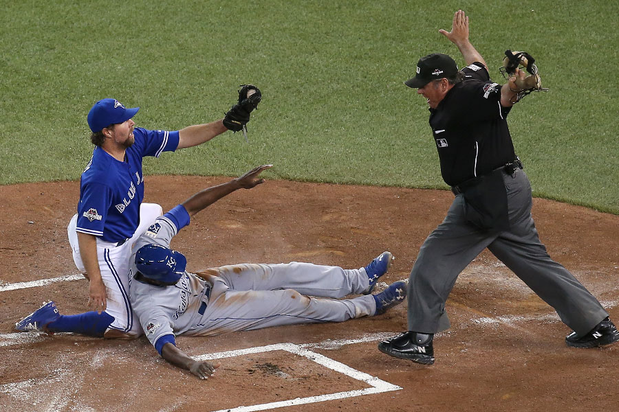 Lorenzo Cain beats the tag by R.A. Dickey to score a run in Game 4 of the ALCS as home plate umpire Hunter Wendelstedt makes the safe call