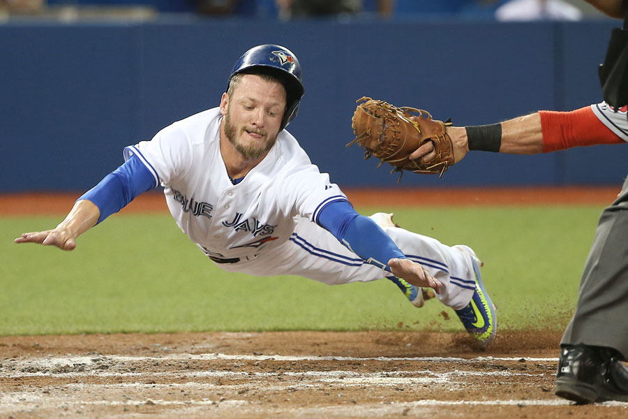 Josh Donaldson slides home past the outstretched glove of Yan Gomes as he tags up and scores a run on a sacrifice fly to the second baseman