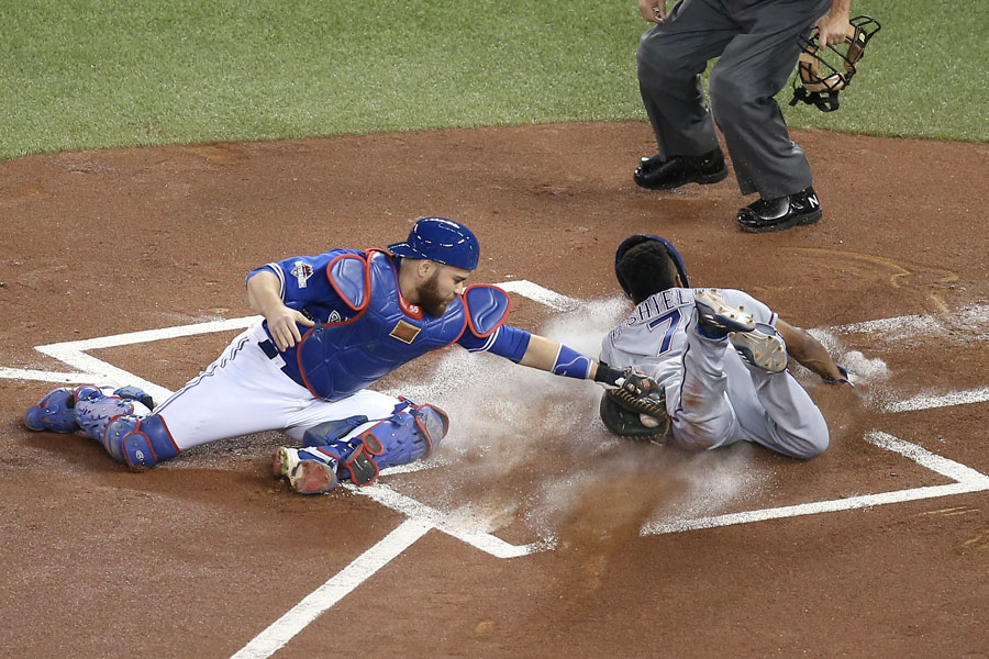Delino DeShields slides across home plate to score a run ahead of the tag by Russell Martin to get things started in the first inning of one of the craziest baseball games ever played in Game 5 of the ALDS