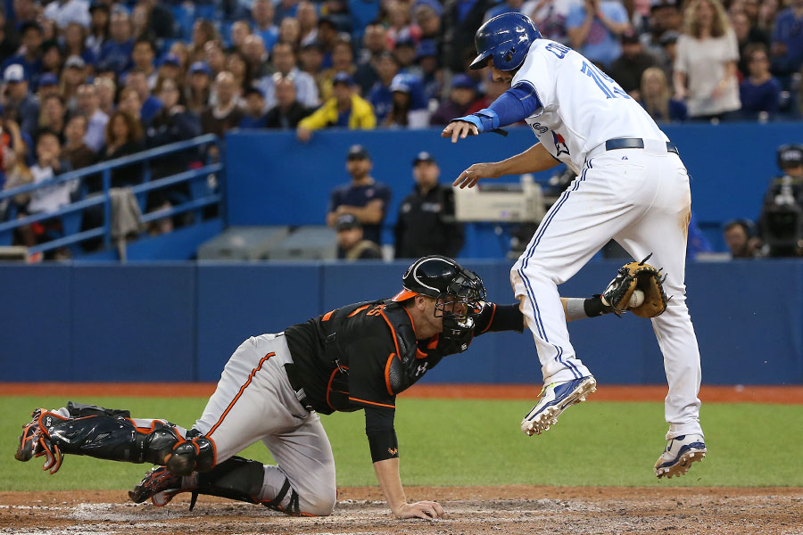 Chris Colabello does acrobatics to try to get around the tag of Matt Wieters as he is gunned down at home plate