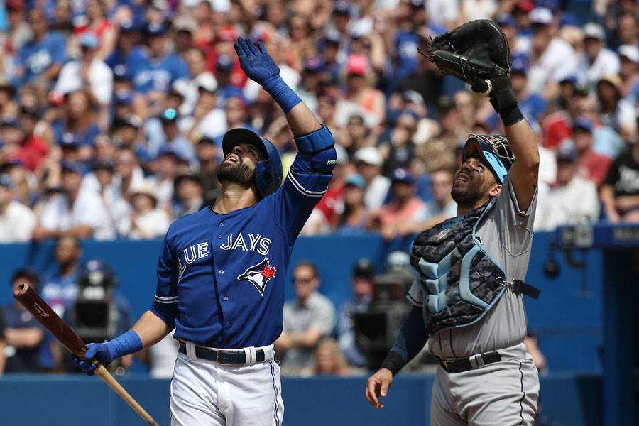Jose Bautista and Rene Rivera shield their eyes as they gaze upwards into the sun while trying to follow the path of Bautista?s foul ball