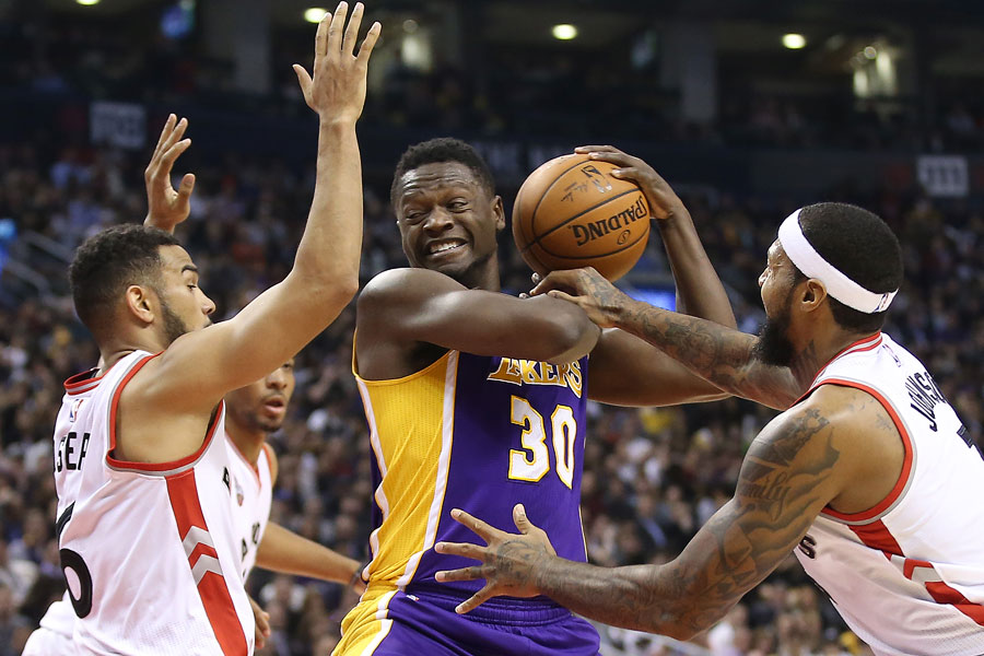 Julius Randle battles to keep control of the ball as he is besieged by Cory Joseph and James Johnson