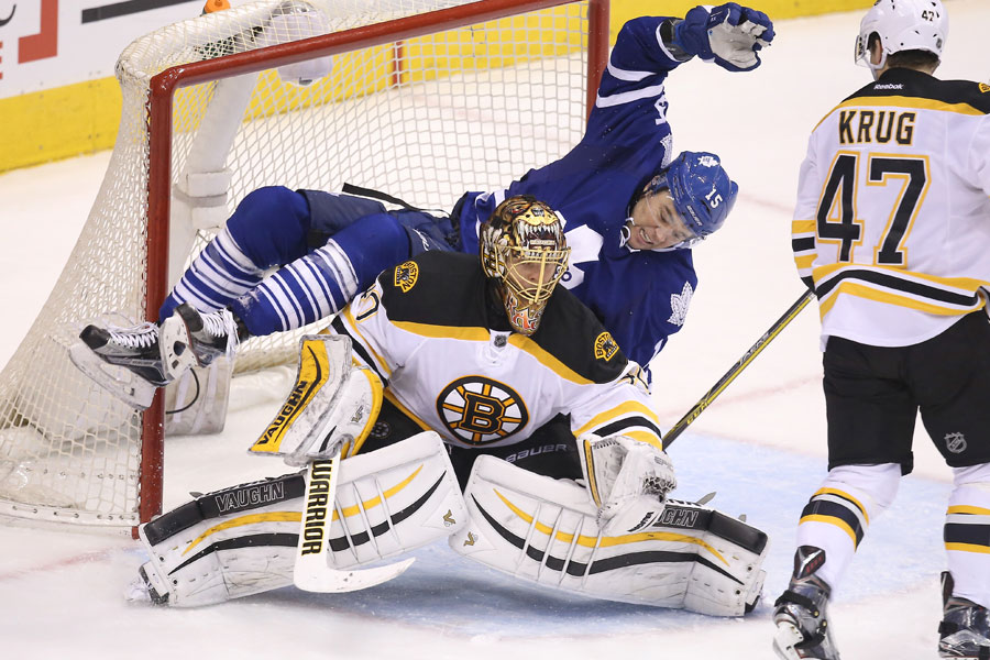 P.A. Parenteau topples over Tuukka Rask as he tries to set up in front of the net