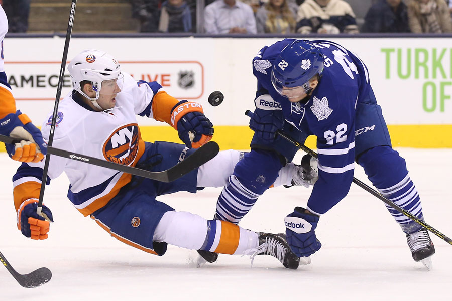 Zach Sill battles for the puck with Josh Bailey who falls