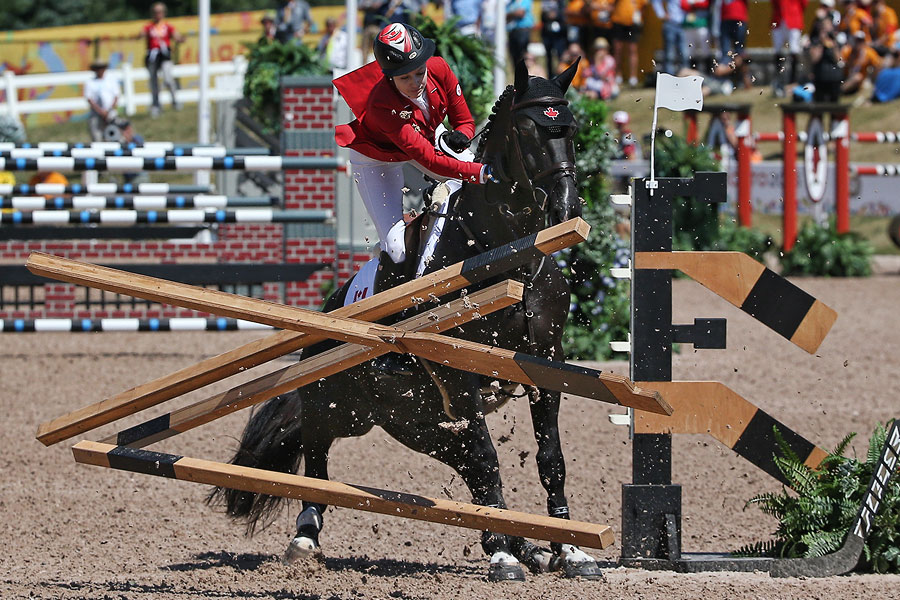 Tiffany Foster (CAN) crashes on her attempted jump in the equestrian individual competition knocking down the hockey stick obstacles during the 2015 Pan Am Games at Caledon Pan Am Equestrian Park