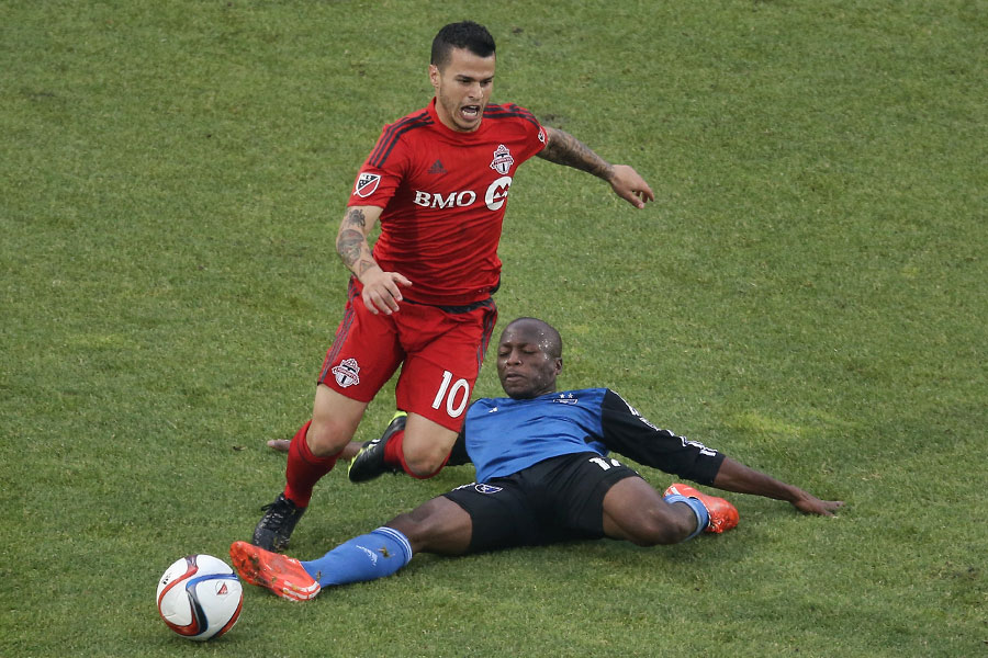 Toronto FC forward Sebastian Giovinco is tripped as he runs with the ball by San Jose Earthquakes midfielder Sanna Nyassi at BMO Field